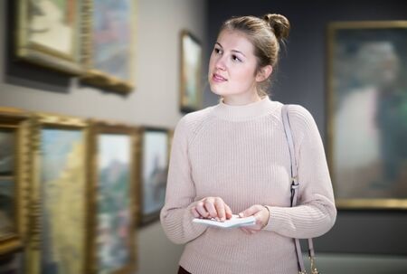 Portrait of ordinary woman looking at pictures and amaze in museum