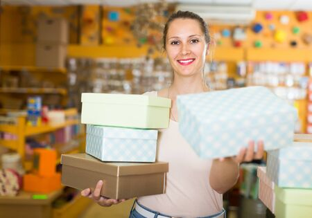 Adult girl with gift boxes in her hands chooses accessories for gift in store