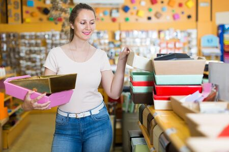 Smiling customer selects boxes and containers for gifts in the supermarket Stok Fotoğraf