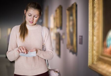 Portrait of young woman with guide looking at pictures in the museum of the arts