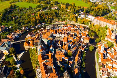 Scenic view from drone of old part of Czech town of Cesky Krumlov with brownish tiled roofs of houses, medieval Castle and Cathedral of Saint Vitus