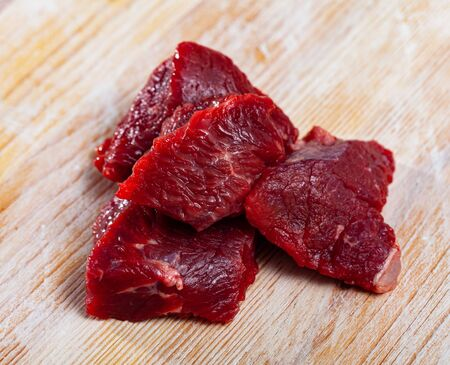 Home cooking. Pieces of fresh raw beef prepared for stewing on wooden table