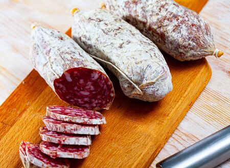 Sliced italian dry sausage salamini on wooden cutting board