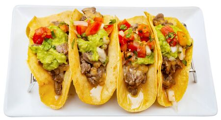 Mexican cuisine. Traditional tacos filled with fried veal, fresh tomatoes and bell pepper, guacamole and salsa. Isolated over white background