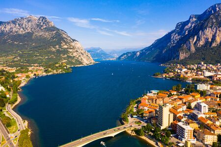 Picturesque view of small city of Lecco on shore of Lake Como on background of San Martino mountain on summer day, Italy