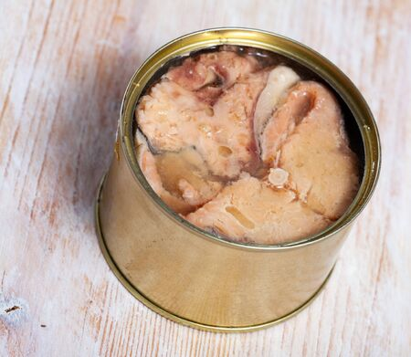 Open tin can with preserved natural humpback salmon on wooden table