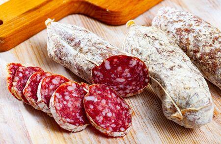 Traditional italian dry cured sausage Salamini italiani alla cacciatora on wooden table 스톡 콘텐츠