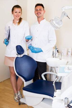 Stomatologist in uniform with assistent are meeting next client by the chair in clinic. Stockfoto