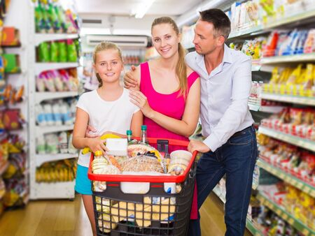 Glad adult family of three smiling and standing with purchases in shopping mall
