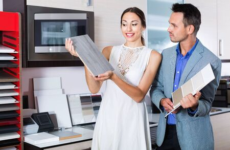 Young satisfied  smiling couple choosing material for facades for their future kitchen