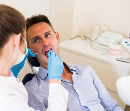 Orthodontist in uniform is examinating adult man on the chair in hospital.