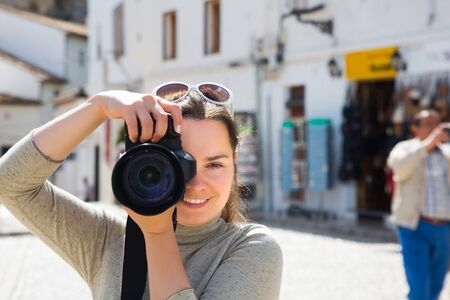Brunette girl with charming smile photographs historic center of city