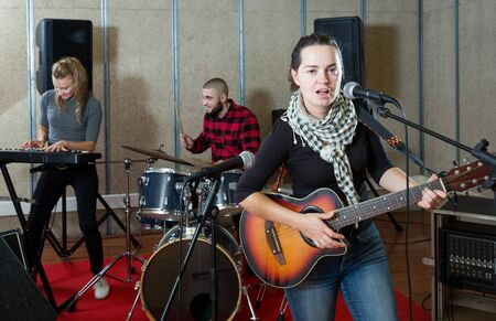 Portrait of active excited adult girl rock singer with guitar during rehearsal with male drummer and female keyboardist in studio Foto de archivo
