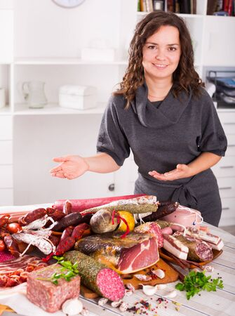 Young brunette girl shows sausages and smoked products which lie on a table