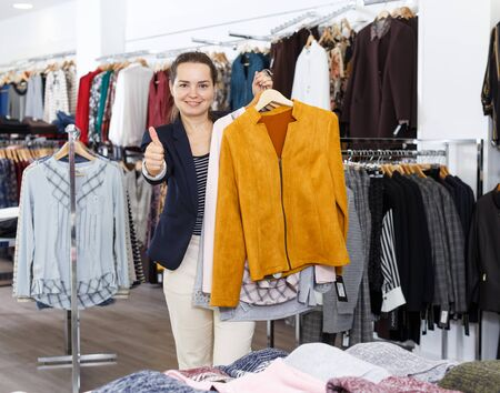 Cheerful attractive woman holding lot of hanger with clothes in showroom