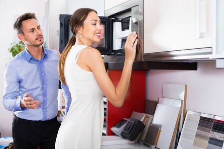 Young happy cheerful couple choosing microwave in household appliance section in furnishing store