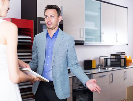 Young confused man with girlfriend making helpless gesture in kitchen accessories store