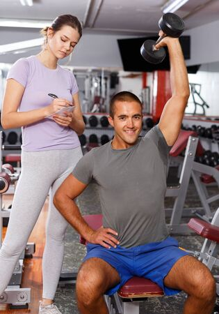 Sporty man and girl checking with workout plan at sports club Reklamní fotografie