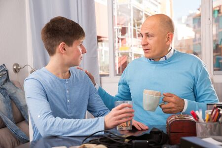 Happy father and teenage son enjoying conversation at home