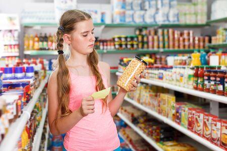Focused tweenage girl doing shopping in food department of hypermarket Stock Photo - 133726359