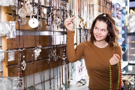 Young girl seller offering colored necklaces and pendants in the store Stockfoto
