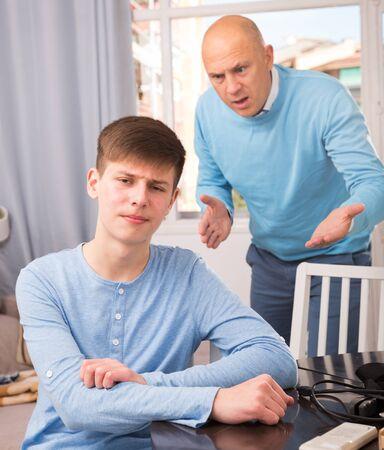 Unhappy man scolding his teenage son at home interior