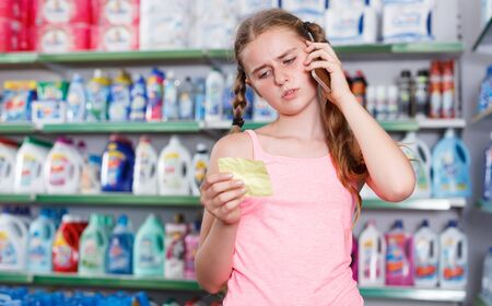 tween girl speaking on mobile and looking at shopping list while visiting supermarket
