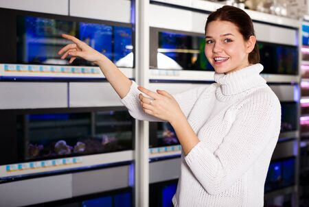 Portrait teenager in aquarium shop points to interesting colored fish on several rows of shelves with aquariums