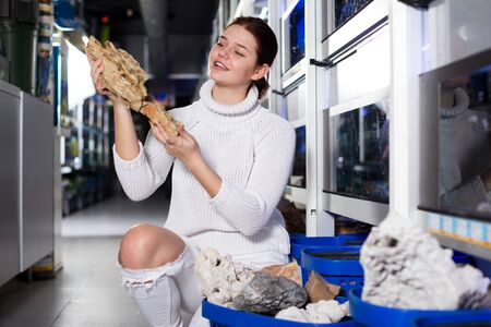 Happy girl in aquarium store holding big yellow-brown sandstone for aquarium decoration Zdjęcie Seryjne