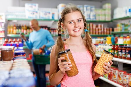 Glad   smiling  tween girl choosing and buying food products at grocery shop