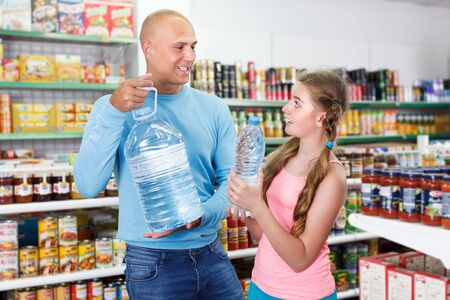 Friendly family with tween girl purchasing together water in bottles in grocery store