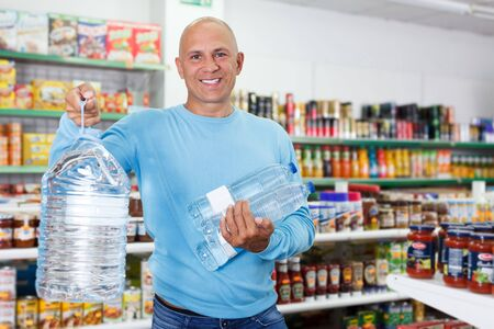 Portrait of positive man buying still water in bottles in grocery shop
