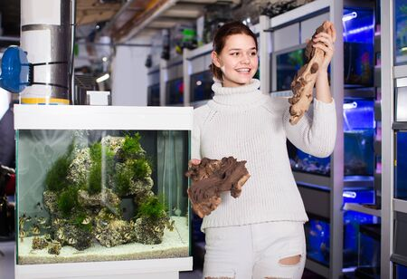 happy girl in aquarium shop choosing brown petrous wood for aquarium decoration