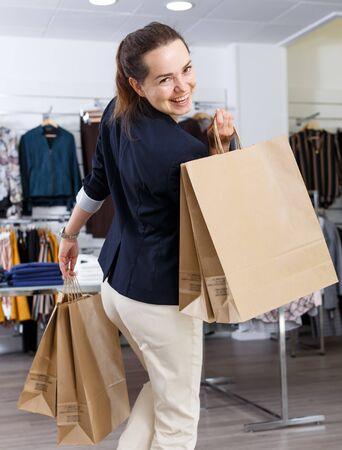 Portrait of modern stylish woman with lot of paper shopping bags in her hands in clothing boutique