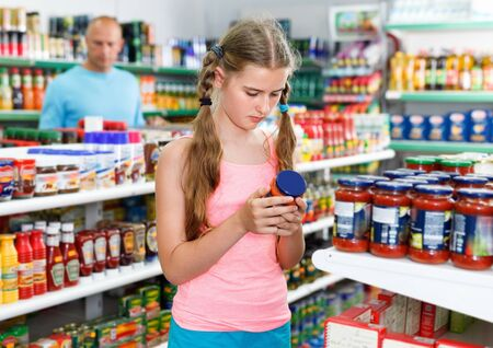 Glad  cheerful positive tween girl choosing and buying food products at grocery shop Stock Photo - 133615658