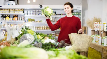 Girl seller shows fresh cauliflower in the grocery store