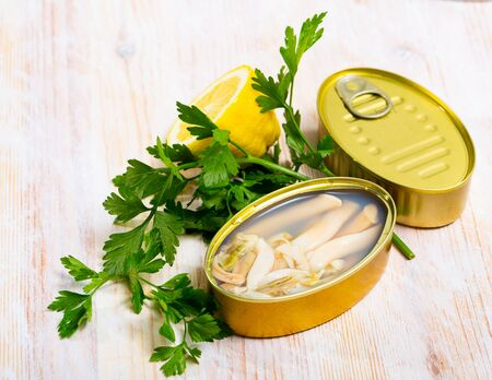 Marinated in oil Navajas shellfish served in tin with lemon and greens
