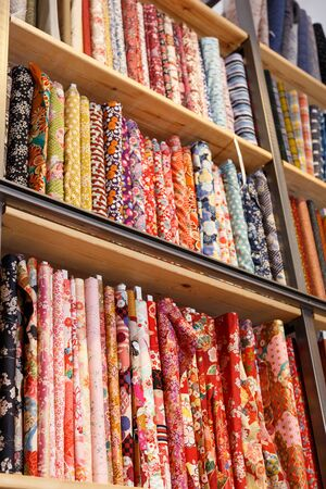 Variety of different fabric bolts exposed on shelves of fabric shop