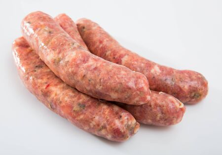 Uncooked homemade sausages with mushrooms on white surface Stock Photo