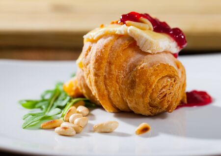 Delicate mini croissant with camembert slice, berry jam, toasted pine nuts garnished with fresh arugula