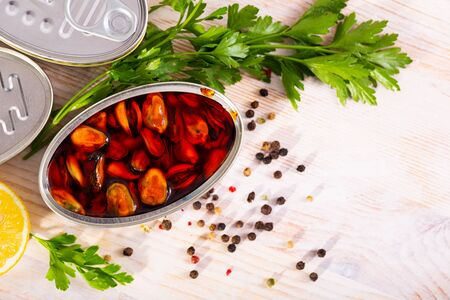 Open can of marinated mussels in spicy oil with herbs and lemon on wooden table