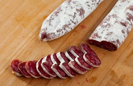 Traditional Catalan thin dry cured pork sausage Fuet sliced on wooden surface