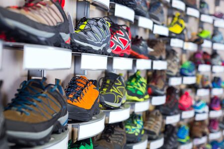Photography of sneakers on shelves of sport store.