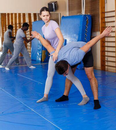 Hombre y mujer joven en entrenamiento de autoprotección, entrenamiento de movimientos de ataque en pareja