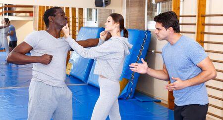 Jeune fille travaillant en binôme avec un homme afro-américain maîtrisant de nouveaux mouvements d'autodéfense avec un entraîneur masculin