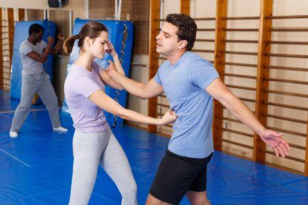 Personas adultas practicando técnicas efectivas de autodefensa en la sala de entrenamiento.