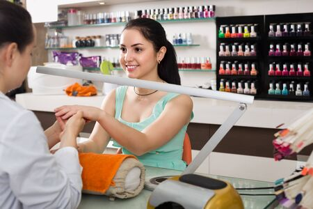positive manicurists giving manicure to female clients at nail salon
