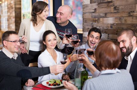 Company of females and males celebrating with food and alcohol drink in restaurant 스톡 콘텐츠
