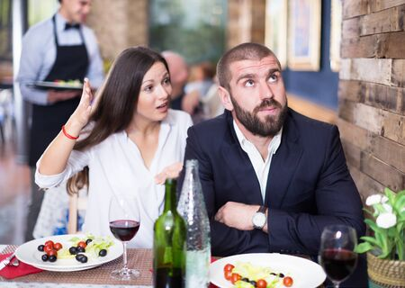 Quarreled visitors female and male in a restaurant on celebrate. Focus on man