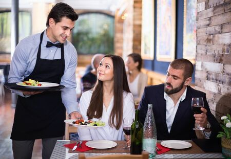 Diligent friendly pleasant waiter with dishes serving man and woman friendly company indoors
